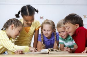 Image of five children looking at a book together