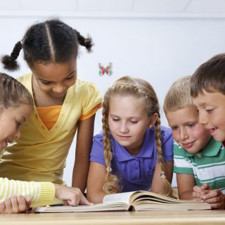 Five young children reading a book together