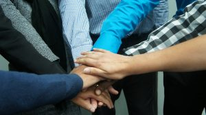 Image of six people putting their hands together