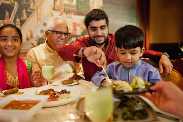 Grandfather, dad, elementary aged daughter and son eating dinner
