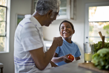 black grandfather laughing with elementary aged child at dinner table