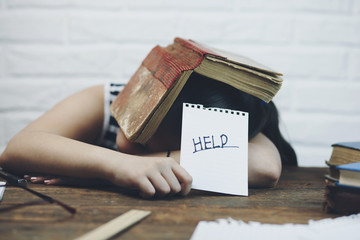 Elementary aged child sleeping at desk with book over head and holding written sign that says Help