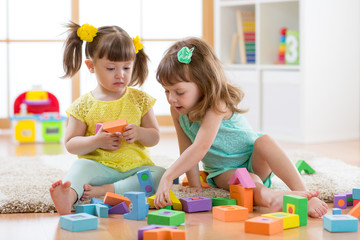 Two toddler aged girls playing with blocks together
