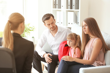 Mom and dad with elementary aged daughter talking with adult female