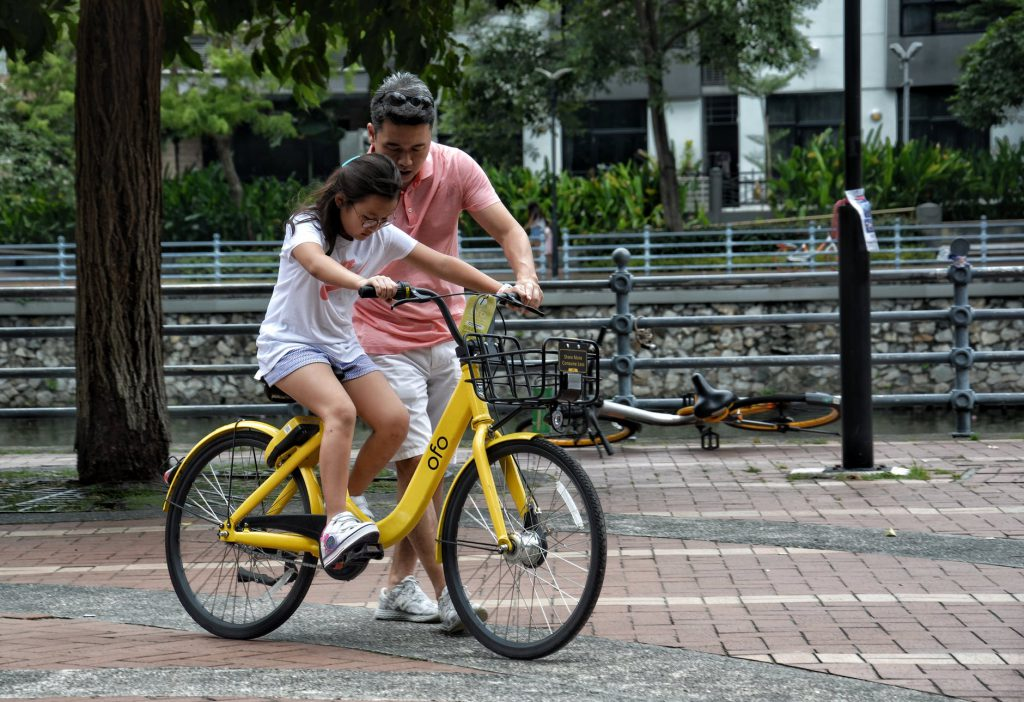 Dad teaching his daughter how to ride a bicycle