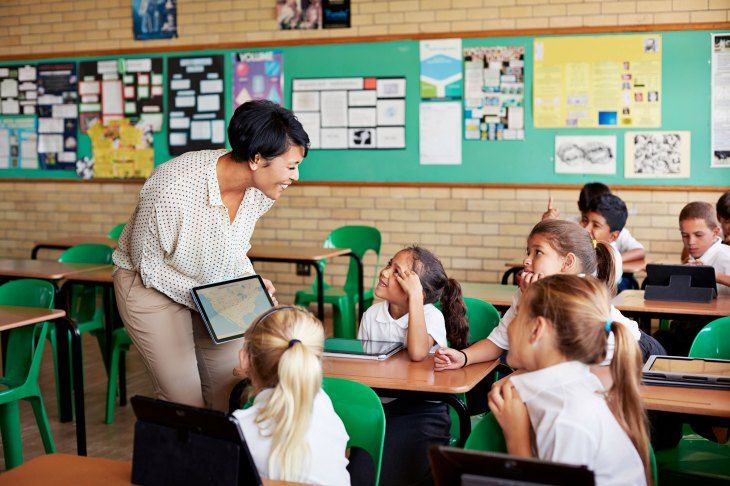 Teacher with IPad talking with elementary aged children in a classroom