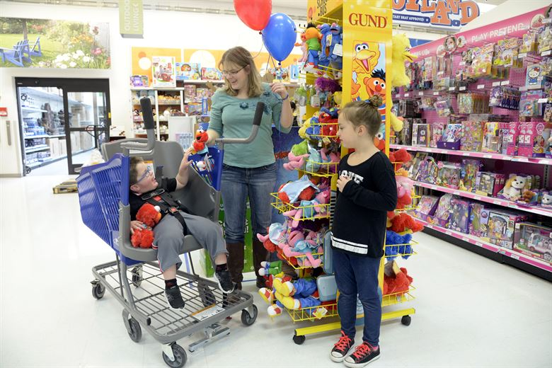 A child in a shopping cart especially designed for children with a physical disability, with his mother and sister by his side