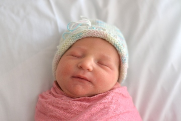 Picture of baby sleeping with knitted hat on and swaddled in pink blanket.