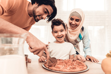 Picture of parents and child at table eating pizza. Dad is cutting the pizza, child in the middle is smiling at camera, mom in hijab is smiling down at the pizza.