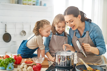 Picture of 2 children and adult in kitchen looking into pot on the stove.