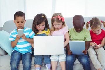 5 children sitting on sofa with various technological items like iPads, mobile phones, and a laptop computer.