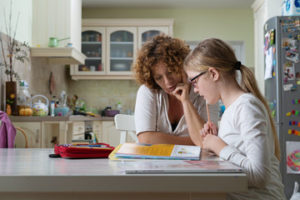 Parent and child at kitchen table doing homework