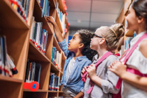 Three young girls looking at books on shelf in library.
