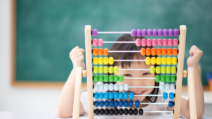 smiling child hides face behind colorful abacus