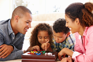 Two parents and tow children playing a board game