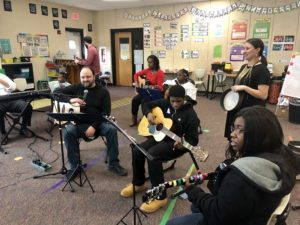 a diverse group of families and students playing instruments together