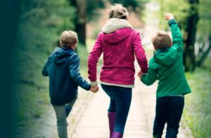 two children and parent walk down sidewalk
