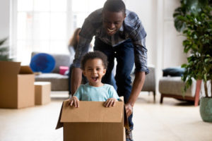 father pushing smiling child in cardboard box