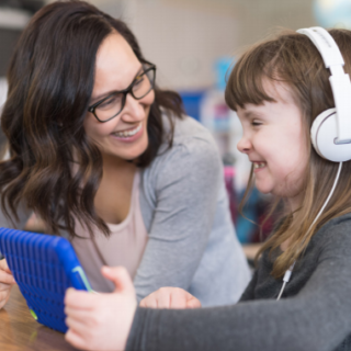 teacher with child wearing headphones and using a tablet