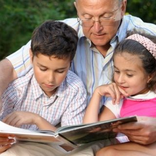 Grandfather reading to two young grandchildren outside