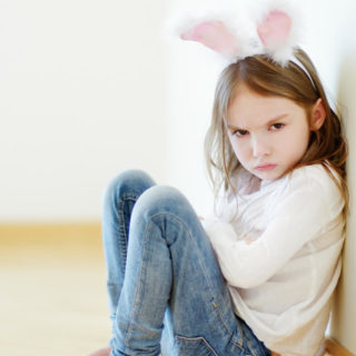 Young white girl sitting with arms crossed and mad face while wearing rabbit ears