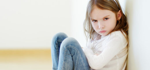 Young girl sitting with arms crossed and mad face while wearing rabbit ears