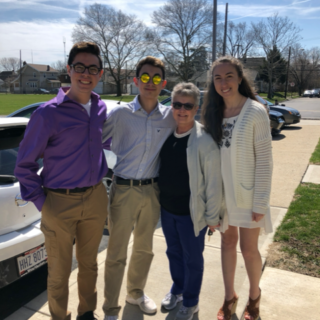 Grandma with three high school aged kids standing outside on a sunny day smiling and looking at the camera.
