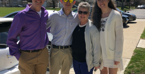 White grandma with three white high school aged kids standing outside on a sunny day smiling and looking at the camera.