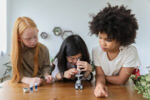 Three girls in first grade taking turns looking in a microscope
