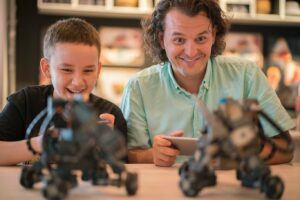 Father and son each playing with a small robot