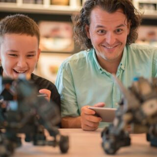 White father and son each playing with a small robot