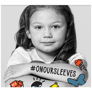 Black and white photo of young girl with #ONOURSLEEVES on her arm