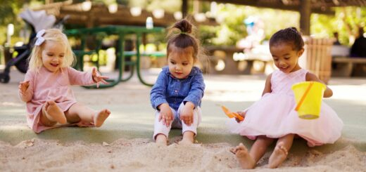 Three toddlers playing in the sand together