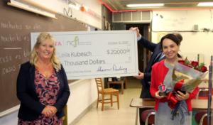 Leila Kubesch receiving a check for $20,000 after winning the Toyota Family Teacher of the Year Award