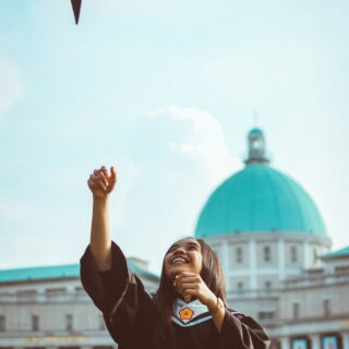 Female Asian graduate tossing her mortar in the air
