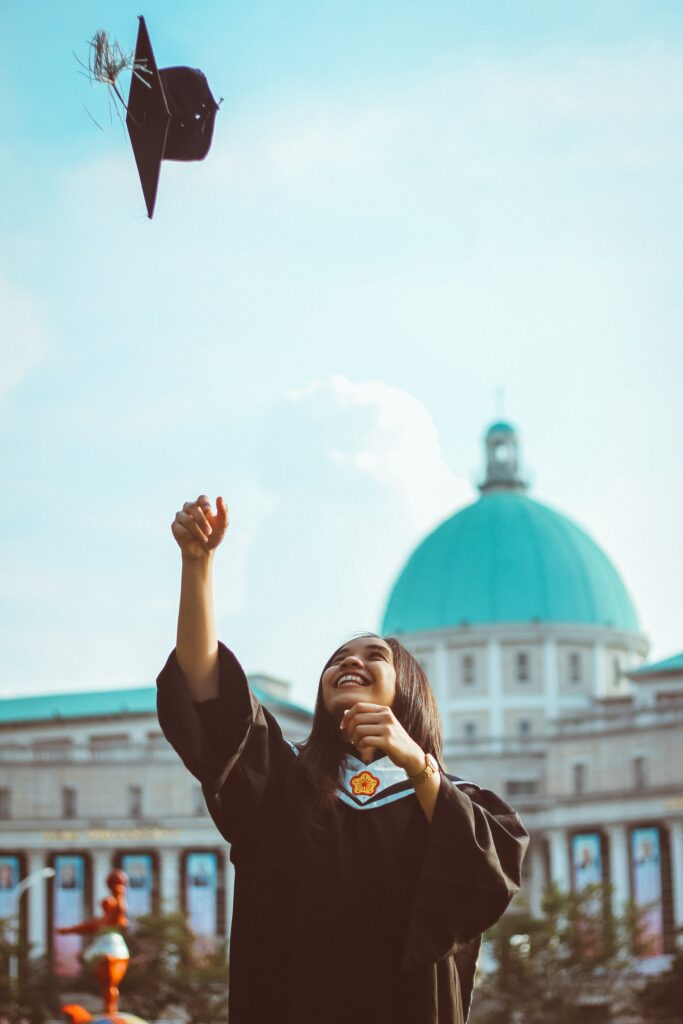 person with long hair and brown skin throwing a graduation cap up in the air