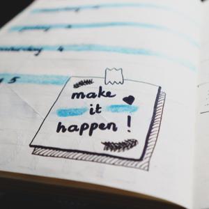 Doodle on paper that says make it happen!