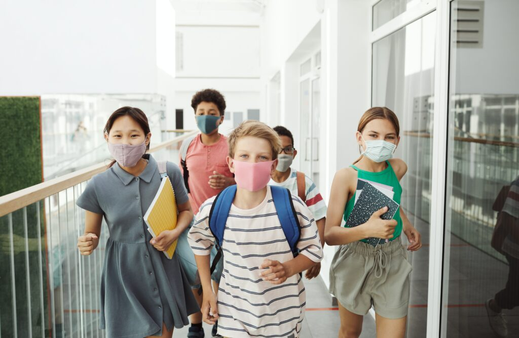 diverse looking group of middle school children wearing face masks and walking with school-related items like backpacks and notebooks