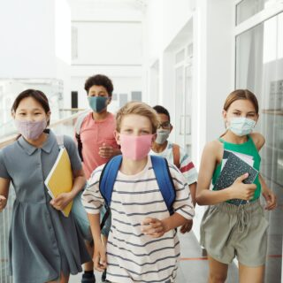 diverse looking group of middle school children wearing face masks at school